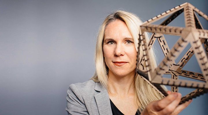 Woman holding a geometric object.