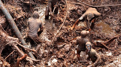 Miners use high-pressure hoses to break down the earth and dredge it up to find gold flakes.